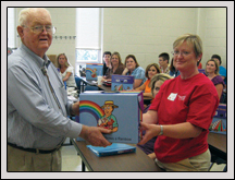 Gaston County Farm Bureau President Bill Craig presents a The Farmer Grows a Rainbow Kit during a teacher workshop in August.