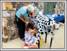 Wake County Farm Bureau Women's Committee Member Monnie Jenks showed children how to milk a cow.