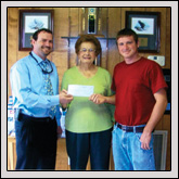 Duplin County Farm Bureau Women's Committee Chair Eva Ketelsleger, center, presents a check to Lee Graham, left, and David Kilpatrick, right, of the Kenansville Fire Department.