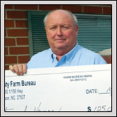 Farm Bureau President Thomas Shaw displays the $125,000 check that was presented to the county for a new Vance County Regional Farmers' Market.