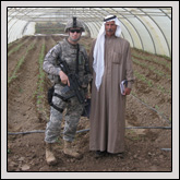 Wake County Farm Bureau Member 1st Lt. John Burt poses with the leader of a local farmers' association in a greenhouse funded with micro-grant money.