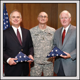 Sgt. 1st Class Ken Colvin presents flags to Steve Carroll (left), general manager of NCFB Mutual Insurance Company, and Farm Bureau President Larry Wooten (right). The flags were flown in Iraq.